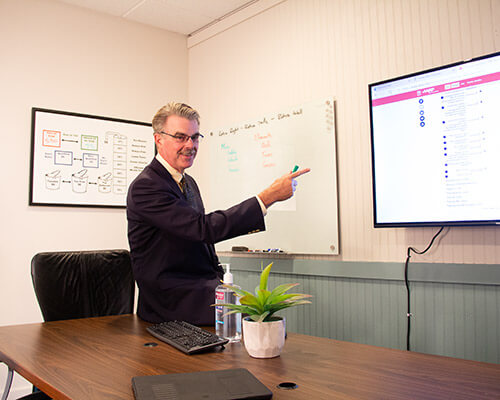 Mark Coker pointing to a tv with financial information on it