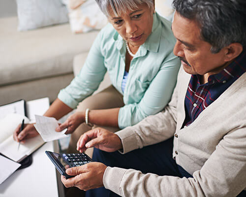 Mature couple using a calculator speaking about money